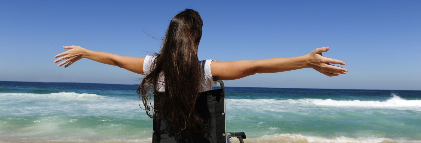A young woman enjoying the beach in her wheelchair.jpg